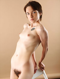 Roberta poses with a white chair naked girls in bed